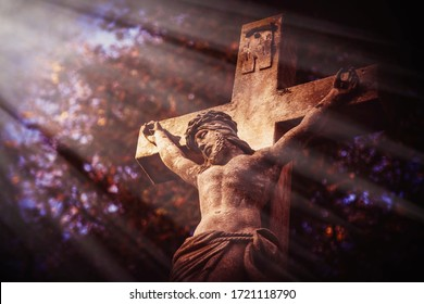 Ancient stone statue of the crucifixion of Jesus Christ in the sun's rays. Faith, religion, suffering, God concept.