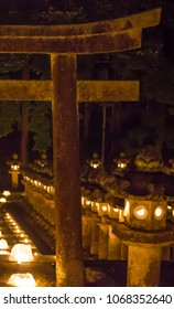 An ancient stone torii gate stands in front of glowing stone lanterns at the entrance to a Buddhist cemetery during the obon ('return of dead spirits') festival in Japan.