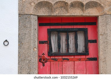 Ancient stone wall with red wooden door