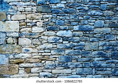 Ancient stone wall texture with blue denim cast.