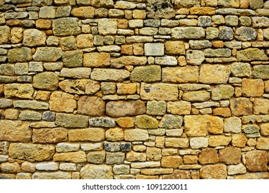 Ancient stone wall texture with orange-yellow cast.