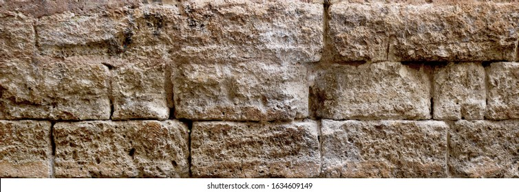 ancient stonewall fort or stronghold - surface of brown rock bricks texture in an horizontal format