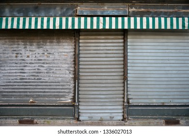 Ancient storefront with metallic closed curtains. Abandoned shop business.