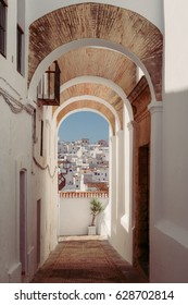 An ancient street with arcs in a White village and the blue sky at the end full of light, a place to go in summer