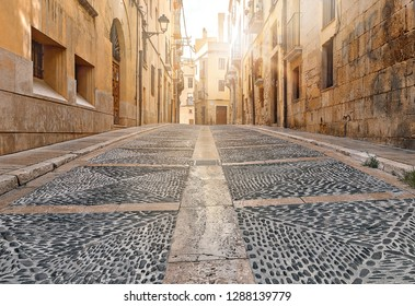 ancient street with gray pavement bridge of ancient Spain city Tarragona on sunny day