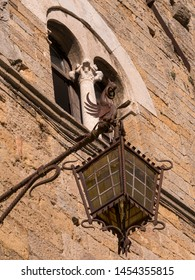 Ancient street lamp with bottom of mullioned windows on the wall of a medieval building in Tuscany, Italy
