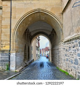 Ancient street. Nice arch. Old Town. Cobblestone road in a medieval city. West Europe.