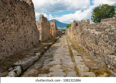 Ancient street in the ruins of Pompeii with Mt. Vesuvius in the background whose eruption buried the city thousands of years ago.
