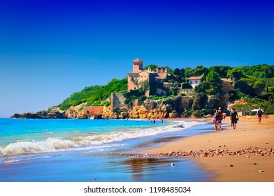 Ancient Tamarit castle overlooking the bright blue Mediterranean sea, Altafulla beach, few walking people, waves rolling on the shore, sand and stones in  Province of Tarragona, Catalonia, Spain