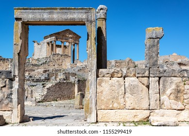 Ancient temple framed by a door in the historic Roman ruins of Dougga in Tunisia