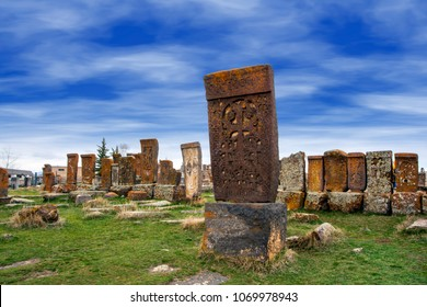 Ancient tombstones known as Khachkars covered with moss and lichen in the Historical cemetery of Noratus in Armenia, near the Lake Sevan under the beautiful blue sky. 10th century