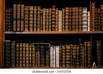 Ancient tomes on an antique wooden bookshelf