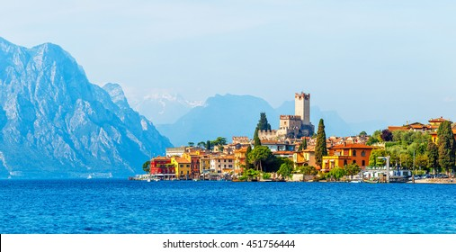 Ancient tower and fortress in old town malcesine at garda lake veneto region italy high snowbound top mountains on background summer landscape with colorful houses green trees