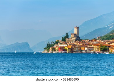 Ancient tower and fortress in old town Malcesine at Garda lake. Veneto region. Italy. High snowbound top mountains on background. Summer landscape with colorful houses green trees