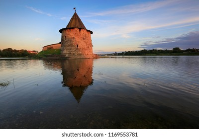 Ancient tower of the Pskov Kremlin with reflection in the river in the evening, Pskov, Russia