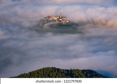 Ancient town with bell tower and old buildings on the top of a hill with clouds around. Magic landscape in Croatia