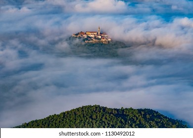 Ancient town Buzet with bell tower and old buildings flying above clouds. Unusual landscape of tourist destination in Istria, Croatia