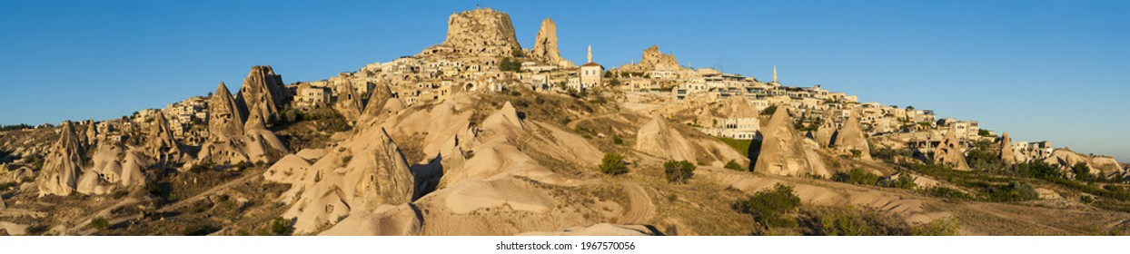 Ancient town and a castle of Uchisar dug from a mountains after sunrise, Cappadocia, Turkey.Panorama - Shutterstock ID 1967570056