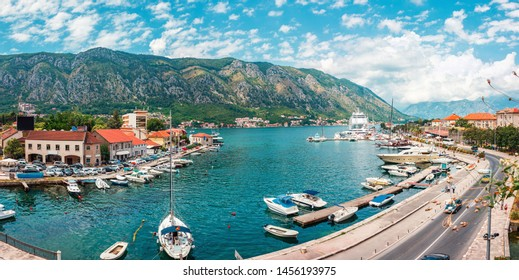 Ancient town Kotor with marina and yachts on the water, old stone houses surrounded by mountains, Montenegro. Panoramic view.