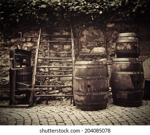 Ancient traditional wine press and oak barrels on Italian street outside restaurant. Traditional old technique of wine-making.