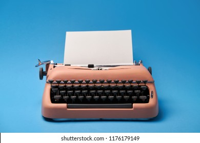 Ancient typewriter with a paper sheet on the blue background in the studio. Closeup. Horizontal.