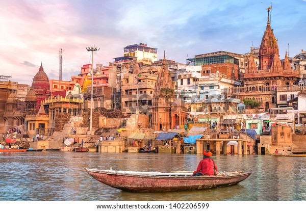 Ancient Varanasi city architecture at sunset with view of sadhu baba enjoying a boat ride on river Ganges.