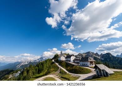 Ancient village of Monte Santo di Lussari (1790 m) and the peak of Mangart (2677 m.) in the Julian Alps. Tarvisio, Friuli Venezia Giulia, Italy, Europe