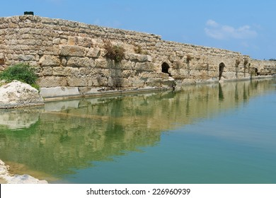 Ancient wall reflecting in the pond in Nahal Taninim archeological park in Israel
