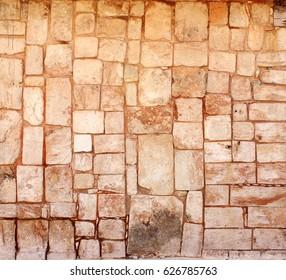 Ancient wall of stone blocks in Uxmal, Yucatan, Mexico