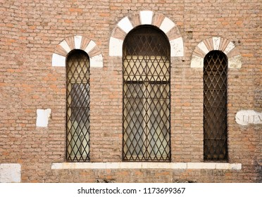 Ancient wall with three windows in Gothic style and stone fragments with Roman unreadable lettering. Lintel stone and brick. Brescia, Italy.