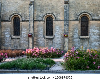 Ancient wall with three windows in Gothic style. Detail of old cathedral  façade with medieval stone brick wall and elongated windows in gothic architecture style, France.