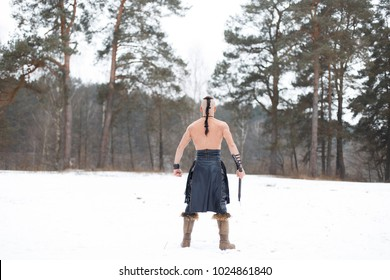 Ancient warrior with an ax in the woods