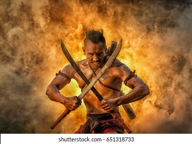 Ancient warrior man of soldier of Bang Rachan District Thailand hold sword fight,Images of dirty middle-aged fighters and swords. Smoke cloud on a black background.Thailand