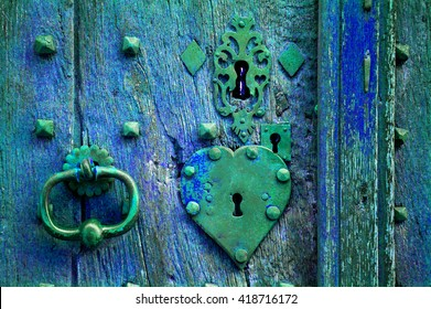 Ancient weathered door with heart shape lock keyhole and handle. Toned photo.