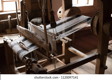 The ancient weaving loom in an interior of a wooden log hut