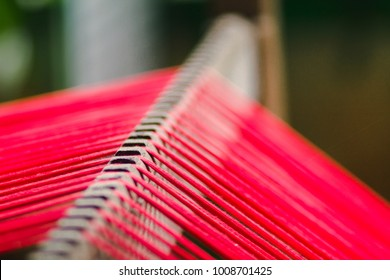 Ancient weaving machine Teak wood is still used for weaving to date and hand-woven works are also popular and expensive.Weaving with red thread prepared for weaving.