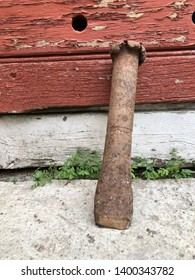 Ancient well used stone mason tool in rusty iron material, leaning on a stone block against a red wooden door.
