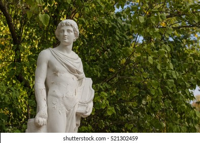 Ancient white statue of Orpheus with a lyre in his left hand in the park against background of tree branches (Central Ukraine)