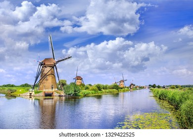 Ancient wind mills near a blue canal on a summer day at the famous Kinderdijk, Holland.