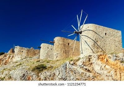 Ancient windmills against a bright blue sky of Lasithi Plateau on Crete, Greece