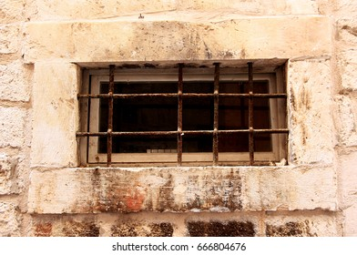 An ancient window with an iron grating in Dubrovnik. Croatia. An ancient window.