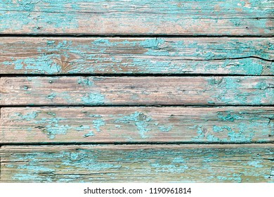 An ancient wooden background with dry peeling paint and large cracks of green and blue.