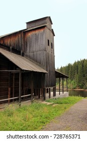 Ancient wooden black building near the lake and forest