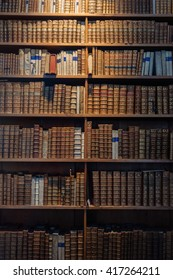 Ancient wooden book shelves with old library books in Vienna, Austria. Dusty bookshelf with rare books collection in bookcase. Retro library photography with antic books