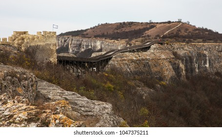 An ancient wooden bridge in a stone fortress through an abyss in the mountains. A wooden bridge connects two rocks of an ancient Bulgarian fortress