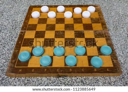 Ancient wooden chess board with blue and white checkers, intellectual game outdoors.