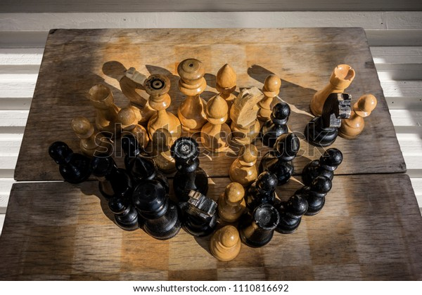 Ancient wooden chess board with vintage figures, intellectual game outdoors.