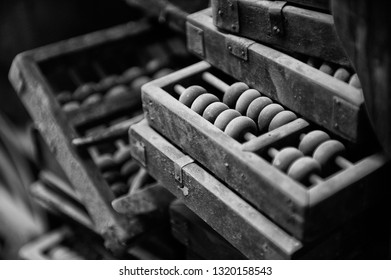 Ancient wooden Chinese abacus covered by dust. Shallow deep of field.