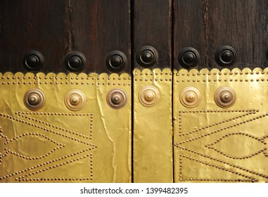 Ancient wooden door with golden brass lower part in a mansion of Seville, Spain.