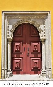 Ancient wooden door on the yellow plastered wall in Sintra, Portugal